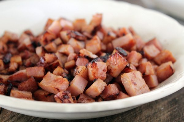 """Call the hogs, people! Football time in Arkansas is here, and so is this awesome recipe for Hot Ham Dip. Or as we like to call it """"Woo Pig Sooie!"""" Dip. Full of browned ham, caramelized onions, and cheese, this Arkansas Tailgate recipe is like crack in a skillet."""