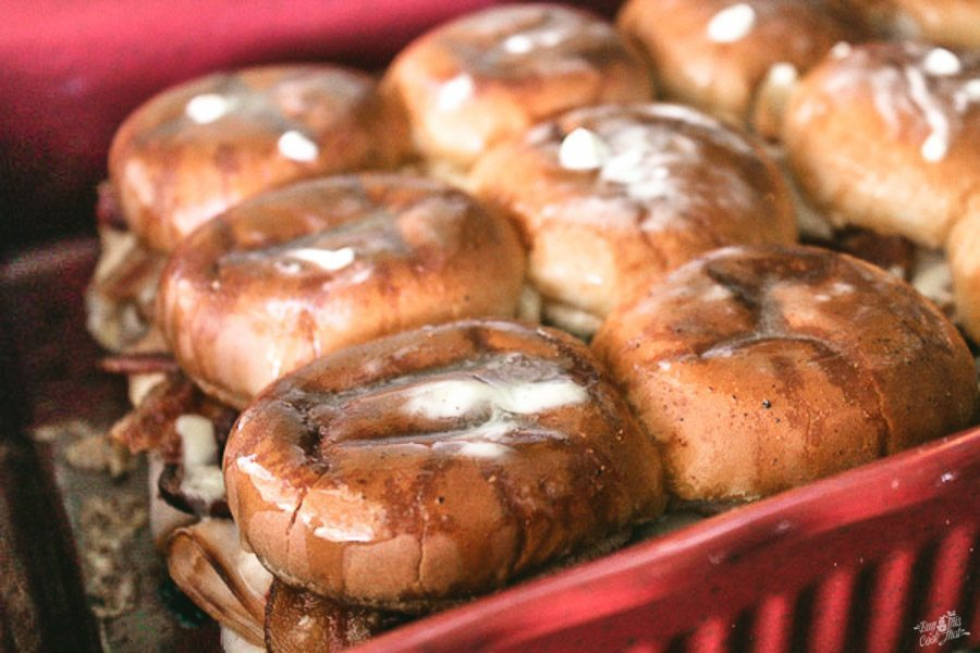 A baking dish full of hot Kentucky brown sliders topped with melted butter and seasonings