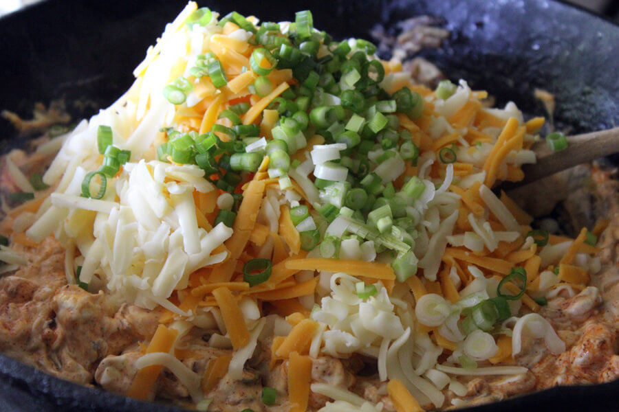 two types of shredded cheese and green onions being stirred into hot ham dip