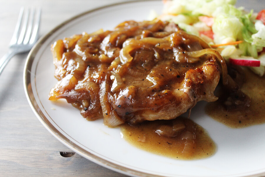 A plate with a smothered and covered onion pork chop