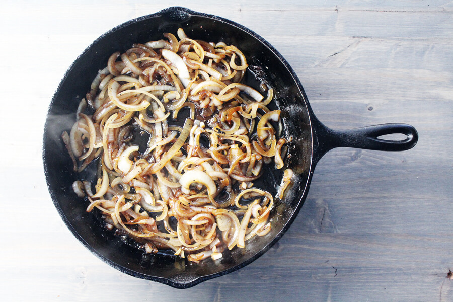 caramelized onions cooking in a cast iron skillet