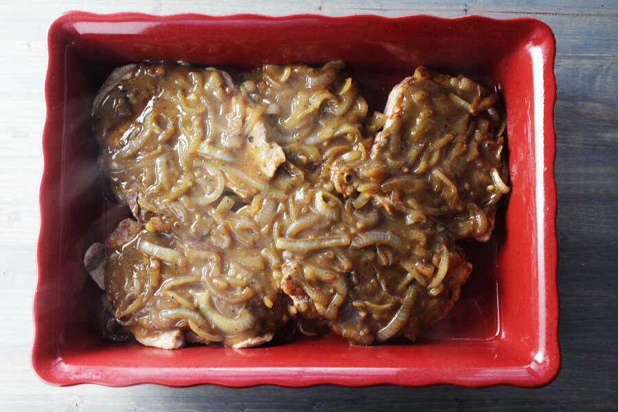 A pan of pork chops covered with onion gravy