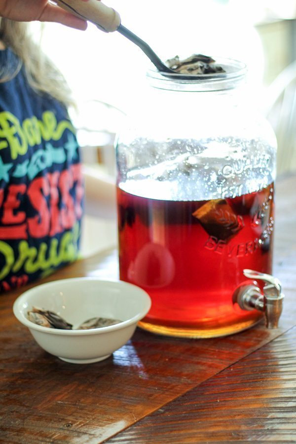 A girl scooping tea bags out of a jug of sun tea