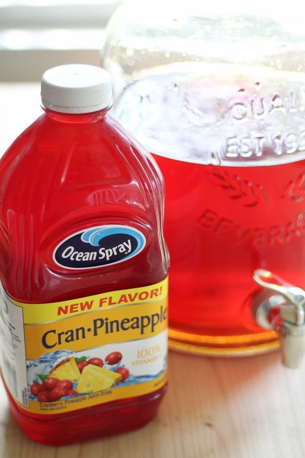 Cranberry pineapple juice next to a container of sun tea