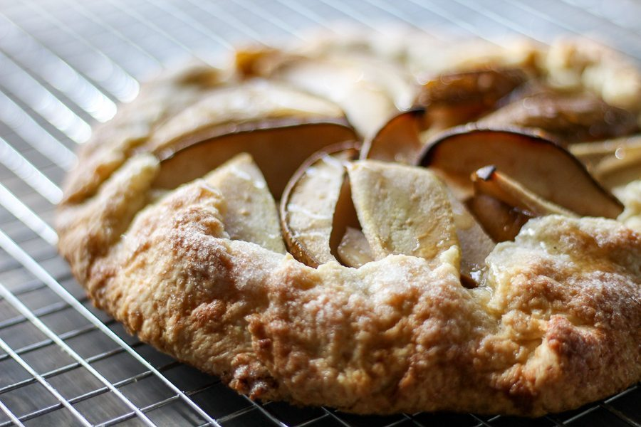 A golden baked pear galette cooling on a wire rack
