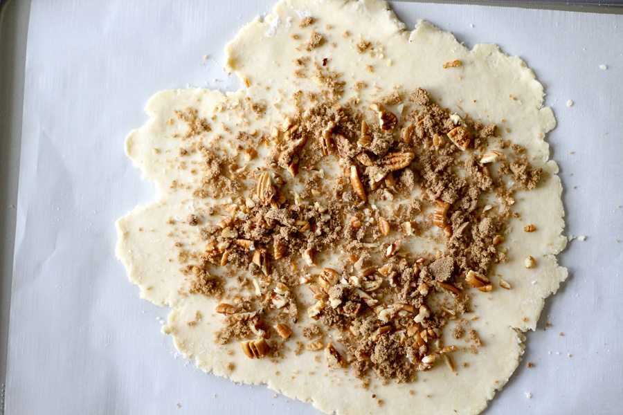 A round of pastry pie dough sprinkled with sugar and chopped nuts