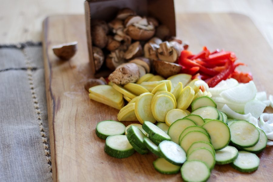 Fresh slices of squash, zucchini, peppers and mushrooms on a cutting board
