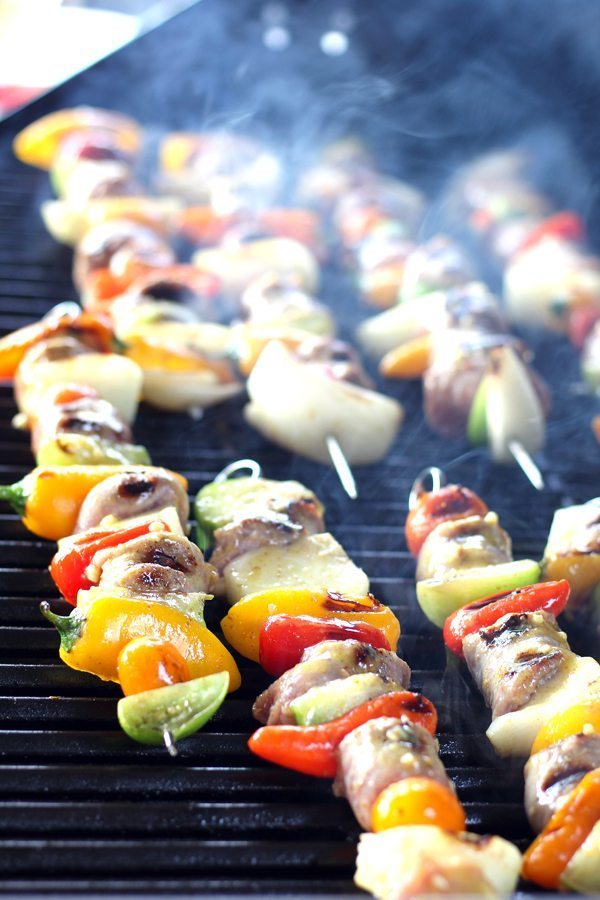 A hot grill smoking with beer brat skewers