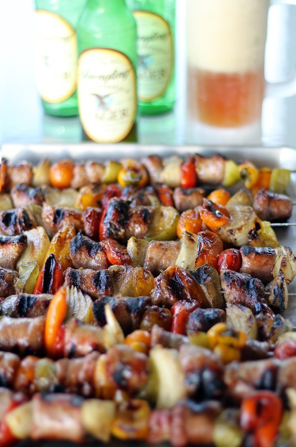 A pan full of Grilled Skewered Beer Brats with Hot Mustard Glaze