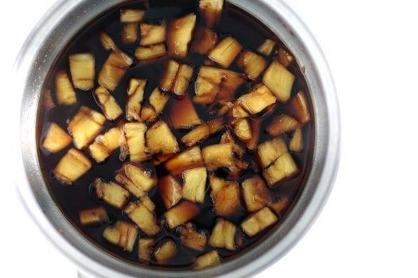 Pineapple chunks simmering in sauce