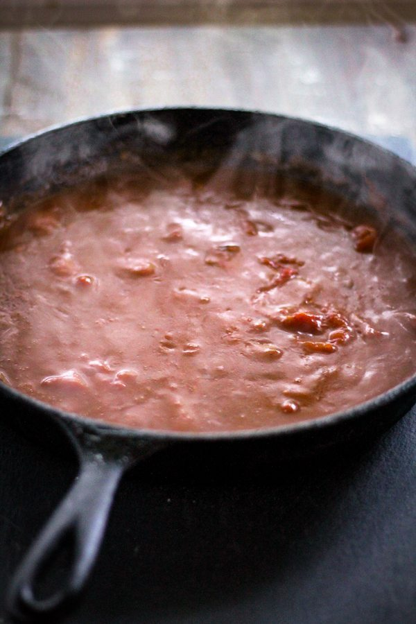 A cast iron skillet with bubbling tomato gravy