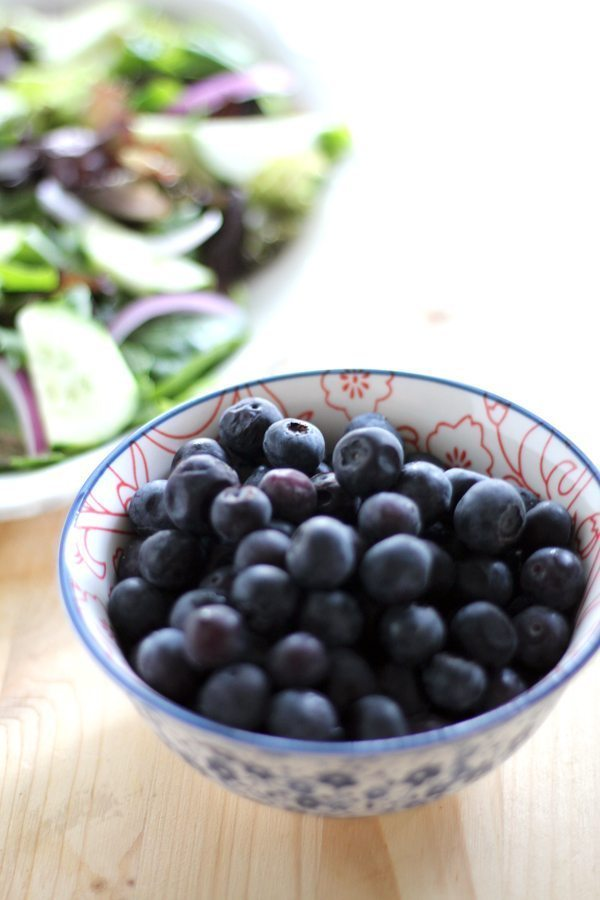 A bowl of fresh blueberries with a tossed salad in the background