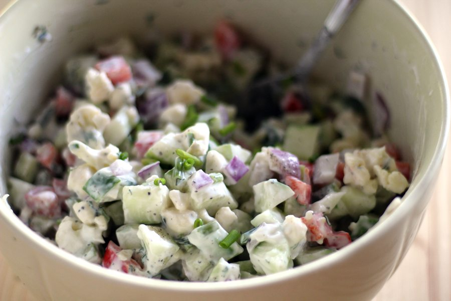 A bowl of chopped fresh cucumbers, red onion and veggies in a creamy Greek yogurt dressing