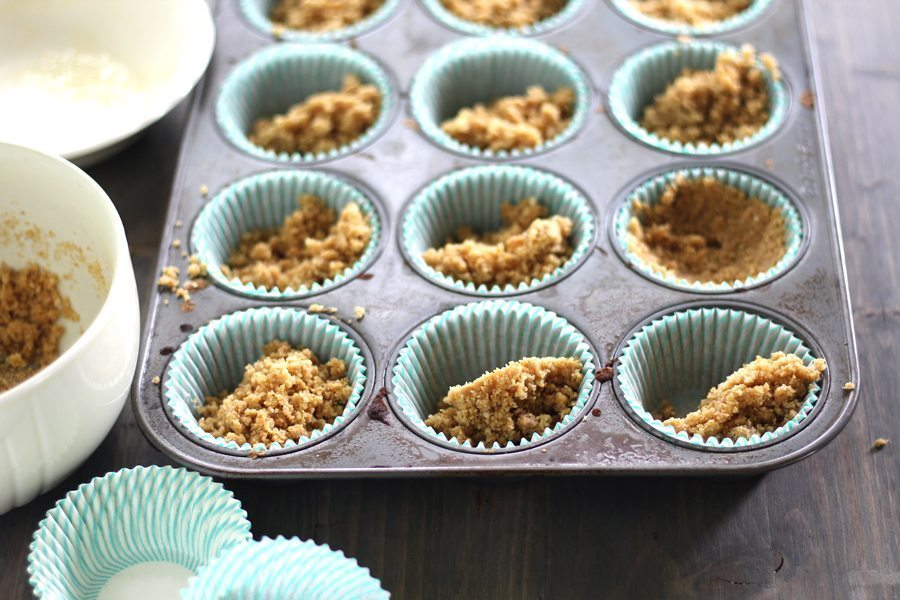 Muffin pan with cupcake liners with graham cracker crumbs pressed into the bottoms.