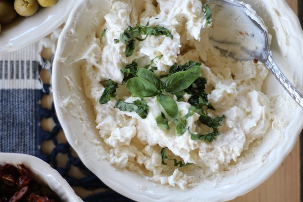 Feta and Asiago cheese spread for bruschetta topped with fresh basil