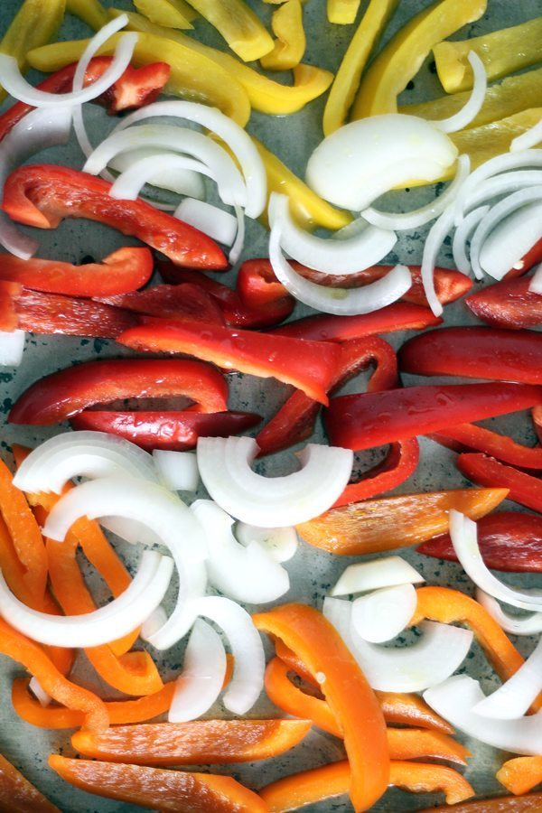 Colorful bell peppers and onions on a large baking sheet