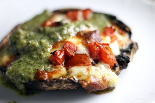 A portabello mushroom stuffed with marinated tomatoes and topped with mozzarella cheese and pesto