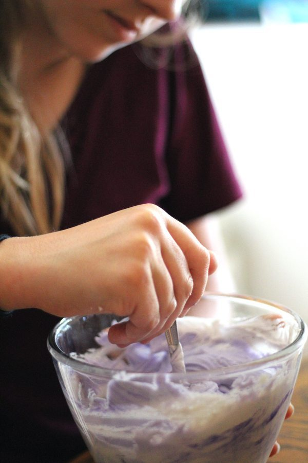 Young girl stirring purple frosting in a glass bowl
