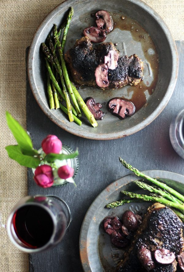 A table set with two plates with asparagus, mushrooms, filet mignon and wine