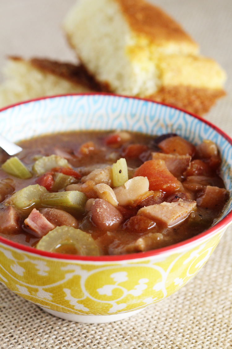 A yellow patterned bowl of ham and bean soup, with a plate of cornbread in the background