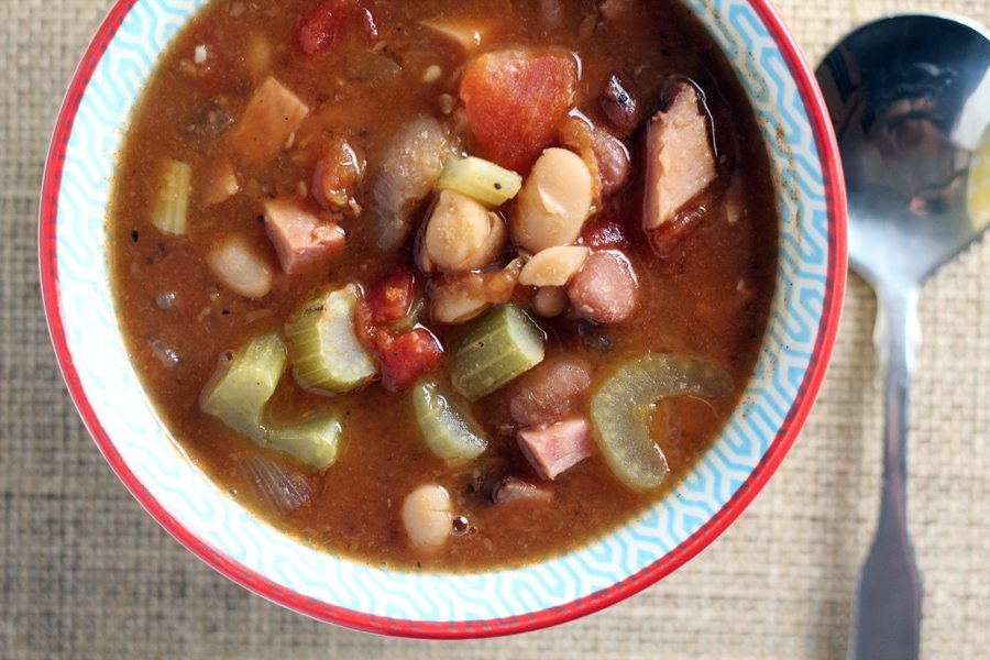 A bowl full of ham and bean soup next to a spoon