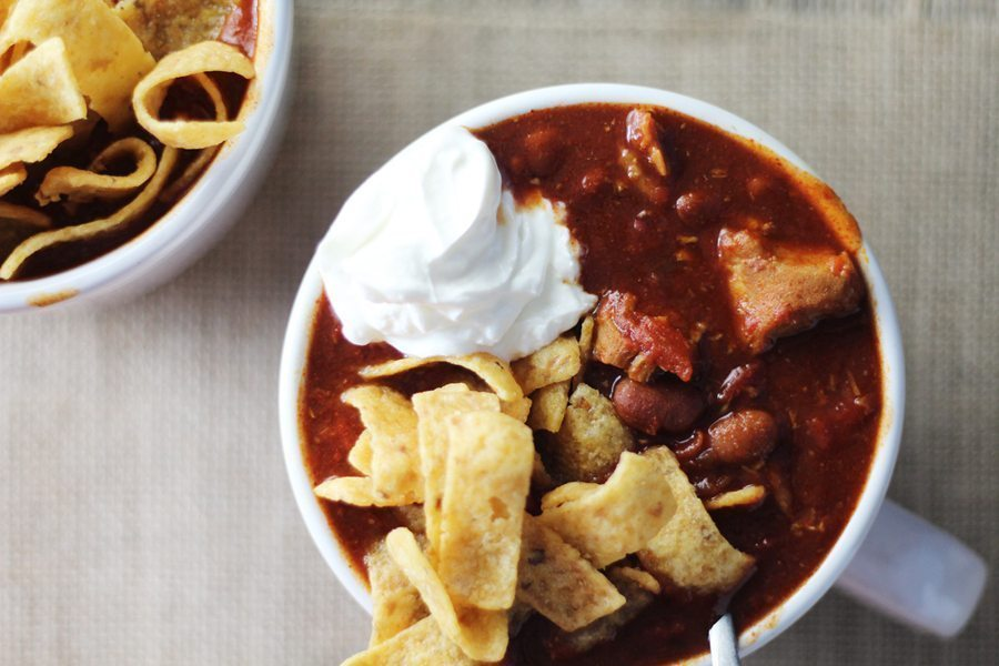 A mug full of spicy BBQ pulled pork chili topped with cheese, sour cream and corn chips.