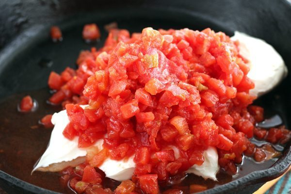 RO*TEL diced tomatoes on cream cheese warming in a cast iron skillet