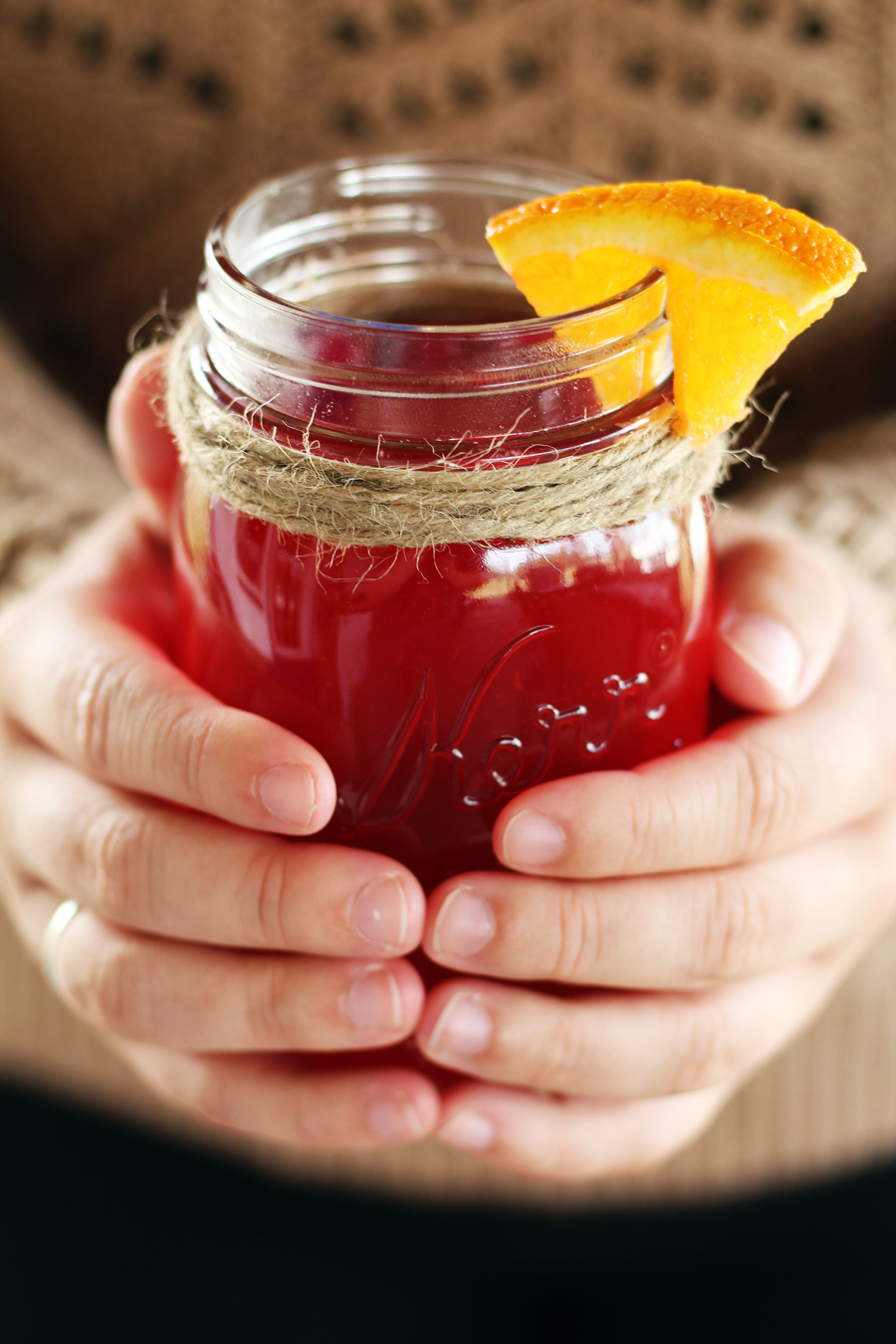 A mason jar of warm cranberry apple cider
