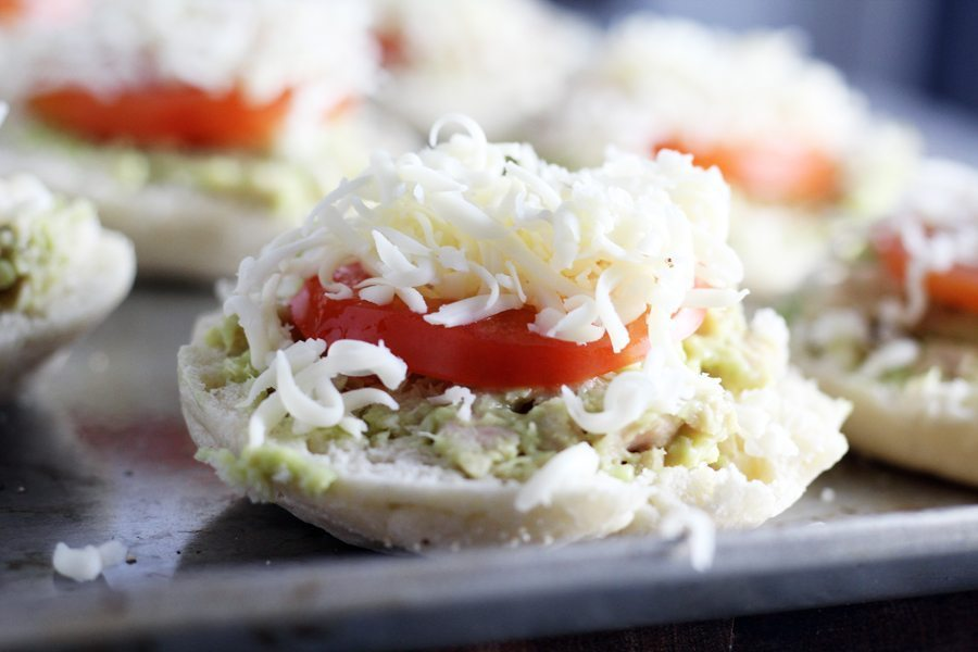An English muffin topped with tuna, avoado, tomato and cheese