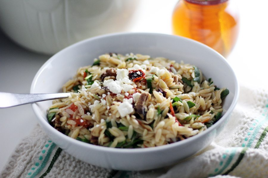Easy and delicious, you are going to love this orzo pasta recipe with tomatoes, spinach, walnuts + feta cheese.