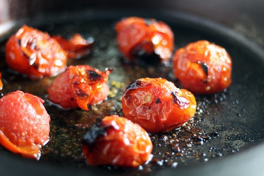Cherry tomatoes roasting in a cast iron skillet