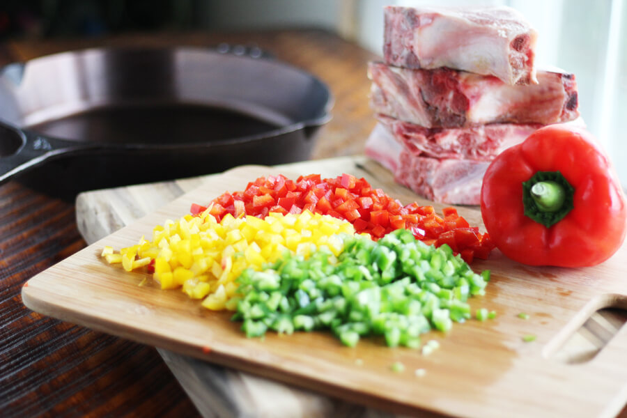a cutting board with fresh chopped peppers in red, yellow and green
