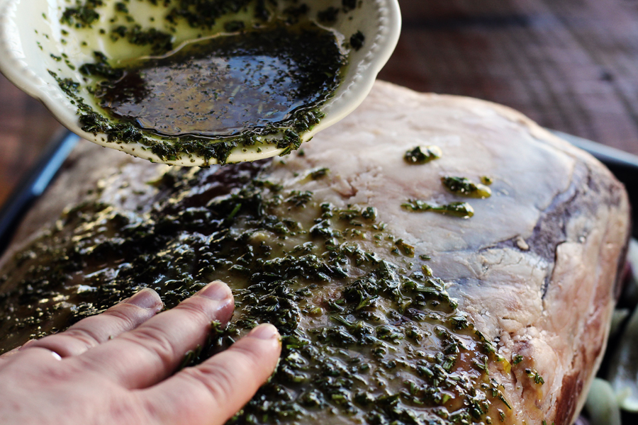 A rub made of seasonings, rosemary, and oil being rubbed on a rib roast