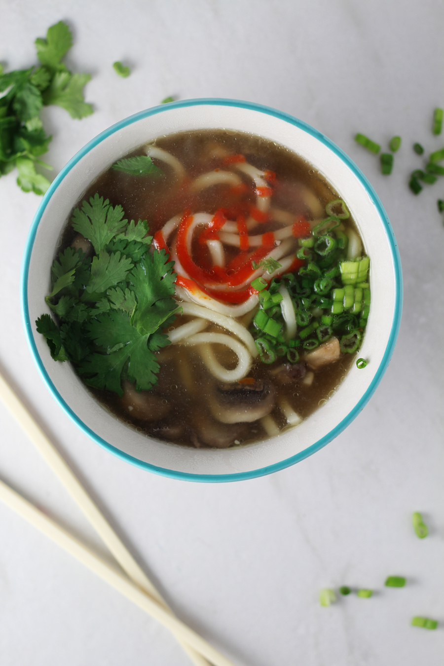 A bowl of ginger broth with udon noodles, and cilantro