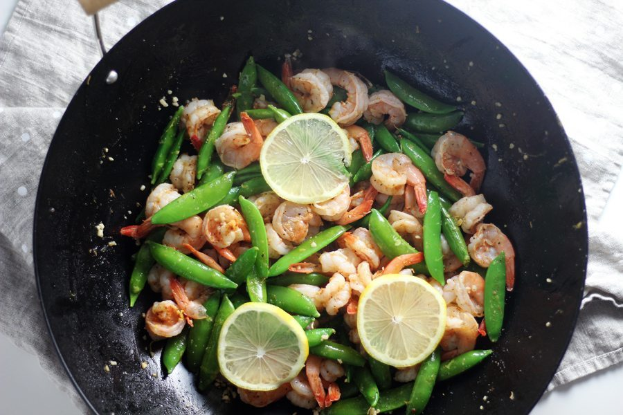 A wok full of shrimp, snow peas and lemon slices