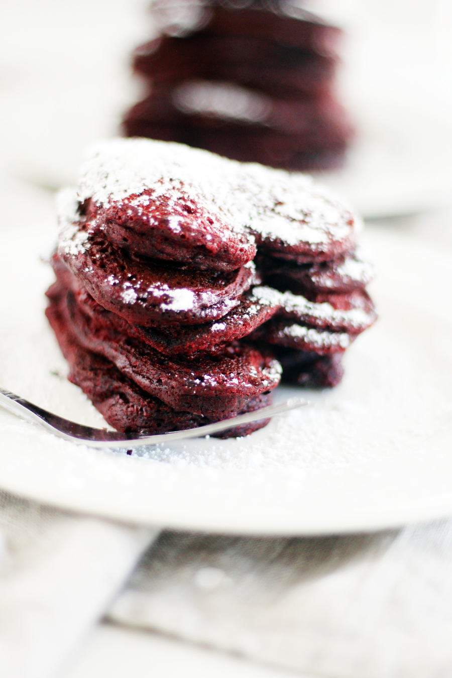 A stack of red velvet heart-shaped pancakes on a white plate, dusted with powdered sugar