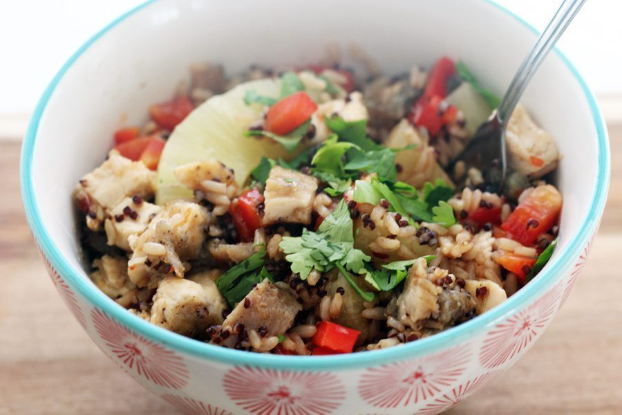 A red and blue patterned bowl with brown rice, quinoa and pineapple