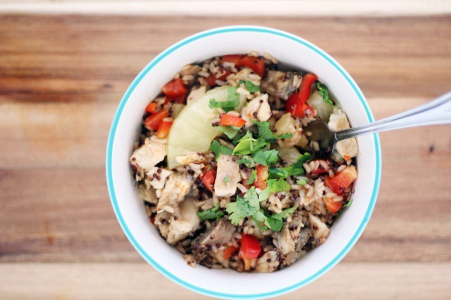 A small white bowl filled with brown rice, quinoa, pineapple, peppers and cilantro