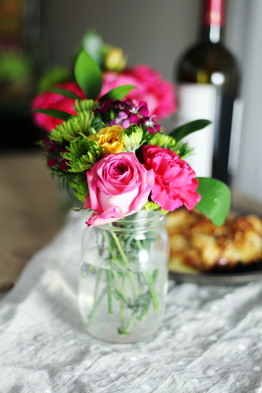 A jar filled with pink roses and assorted flowers, with a bottle of wine and baked brie in the background