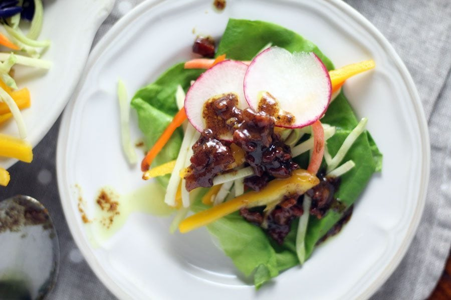 Bacon vinaigrette served on a plate of sliced radishes, belle peppers, and vegetables