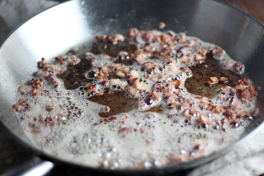 The first step to making molasses bacon vinaigrette is to cook diced bacon until cripsy.