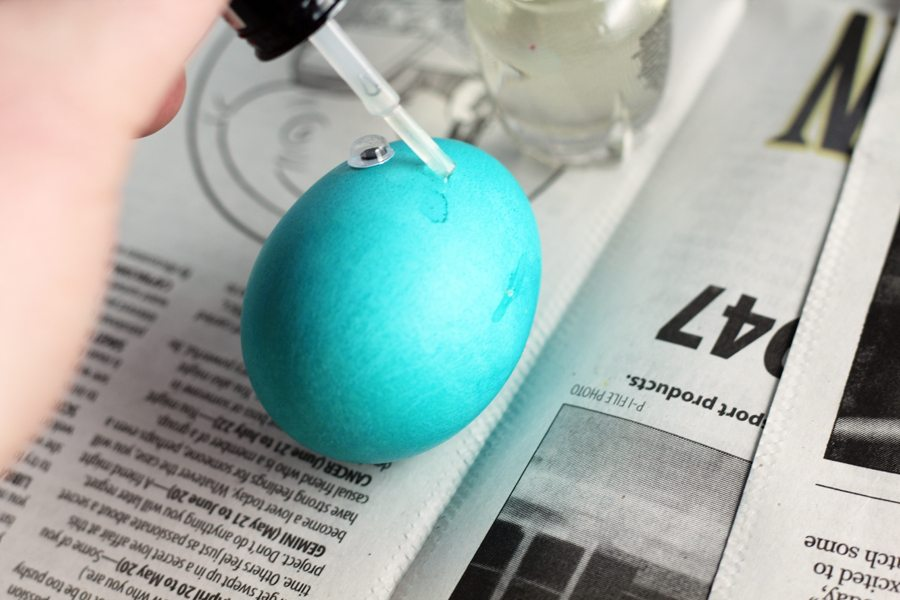 Attaching plastic googly eyes to a blue Easter egg with nail polish