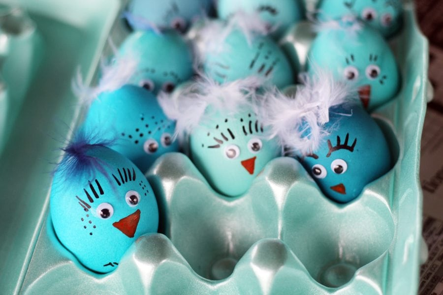 An egg carton full of decorated blue bird Easter eggs