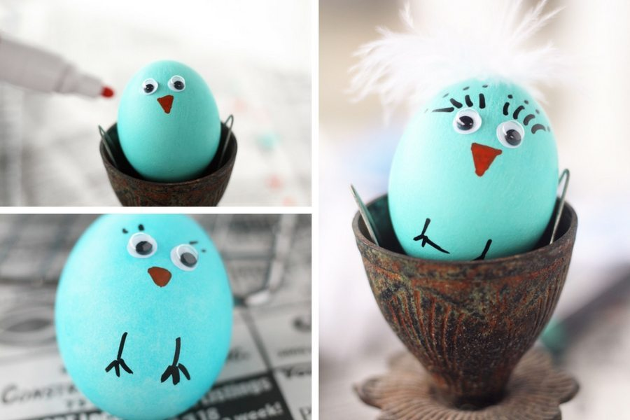 Blue Easter eggs being decorated with hand drawn faces