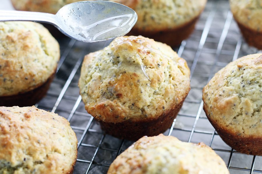 Warm muffins being drizzled with glaze on a wire cooling rack