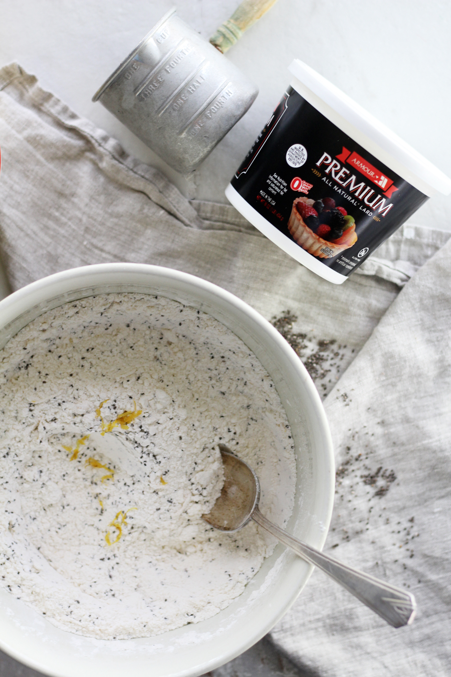 A white bowl of flour and muffin ingredients next to a container of lard and a measuring cup