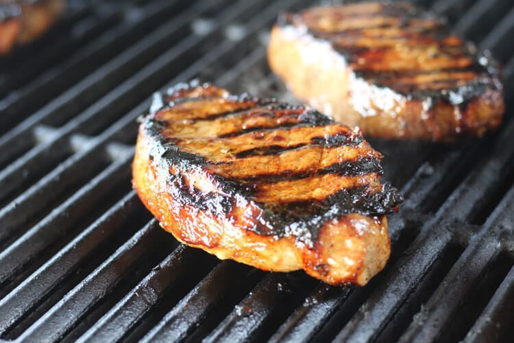 Thick marinated pork chops on the grill with grill marks
