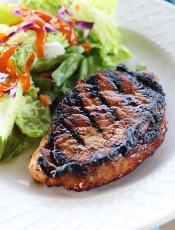 A grilled marinated pork chop on a plate with a salad