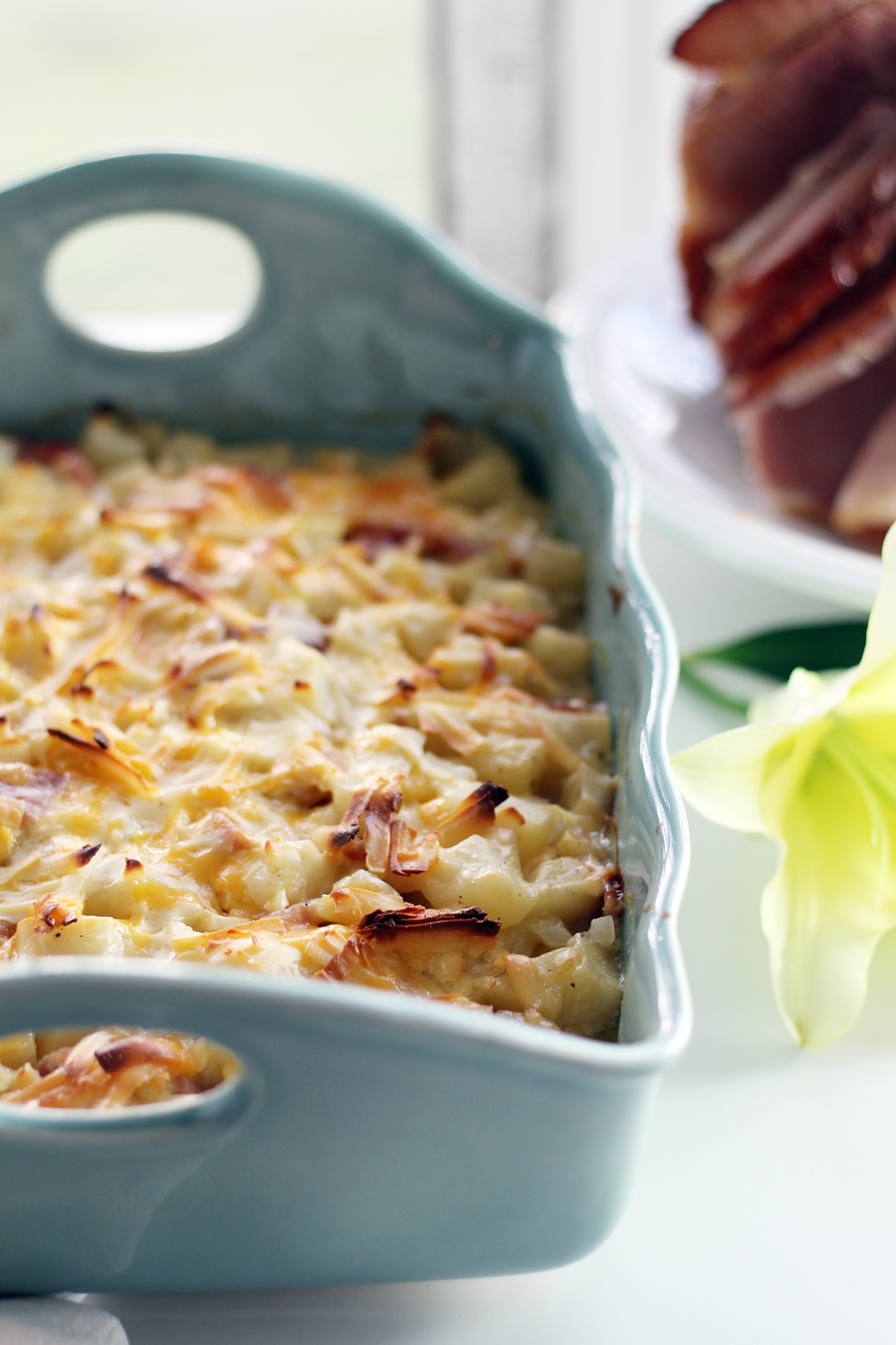Baked potato and ham casserole topped with melted cheese, in a blue baking dish with a honey ham and a lily in the background.