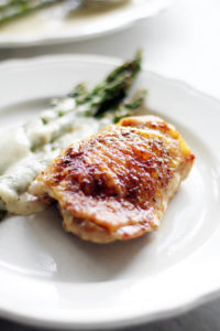 A vertical image of asparagus spears on a plate next to a baked chicken thigh